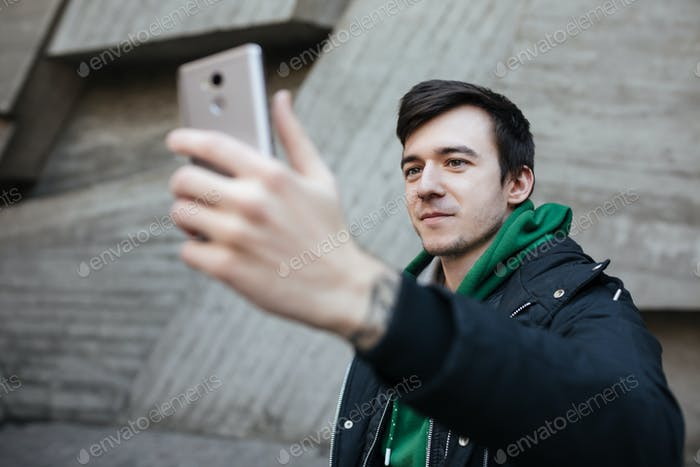 Young smiling man with dark hair in black jacket standing on street with mobile phone in hands