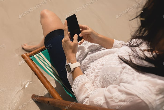 Young woman relaxing on sun lounger and using mobile phone at beach in the sunshine