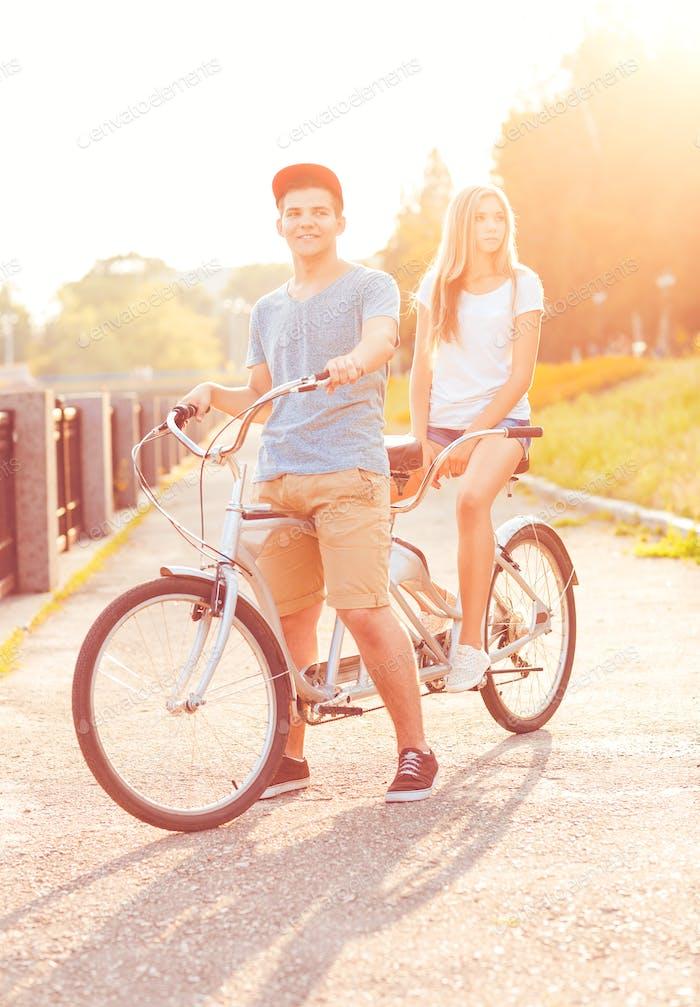 Hombre joven y Mujer montando una bicicleta en el Parque al aire libre