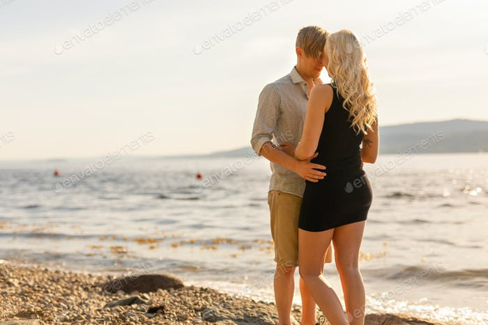 Beautiful young couple in romantic embrace on beach at summer