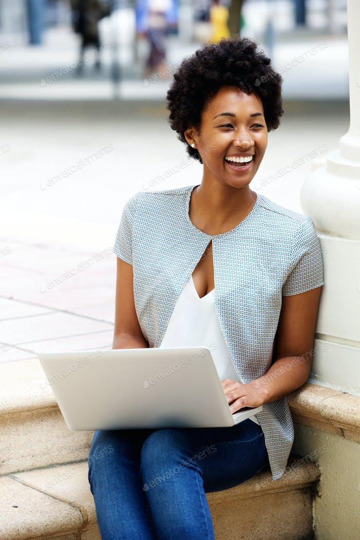 Lächelnde junge Frau sitzt draußen mit einem Laptop
