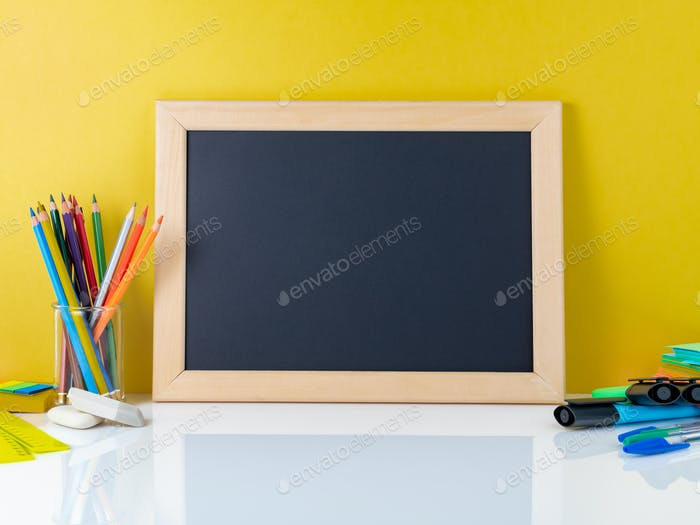 Chalkboard and school supplies on white table by the yellow wall