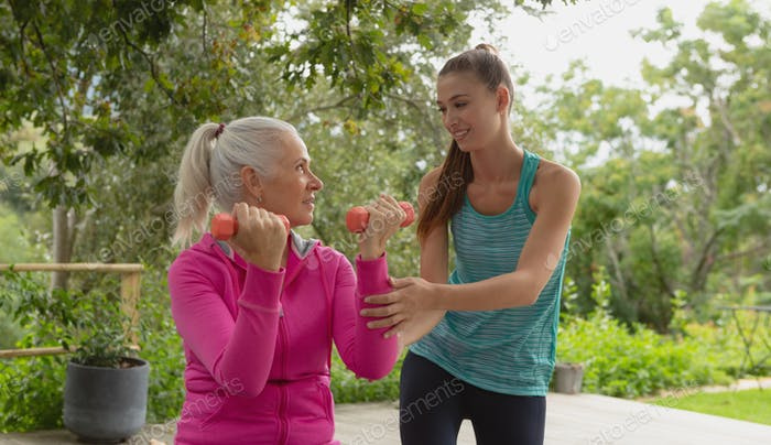 Beautiful Caucasian female trainer assisting active senior Caucasian woman to exercise with dumbbell