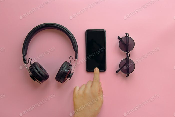 Black sunglasses,smartphone and headphones on pink background