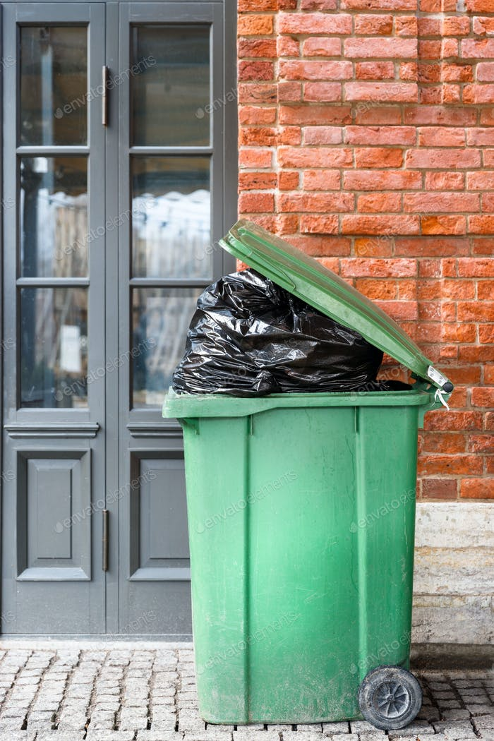 Opened big green plastic trash can with full trash bags. Disposal of waste