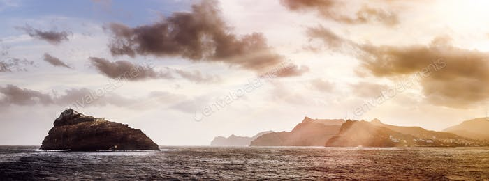 Rocky Atlantic shoreline under dramatic cloudscape. Sunrise on Cape Verde. View from the sea