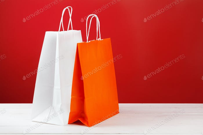 Paper shopping bags with copy space on red background