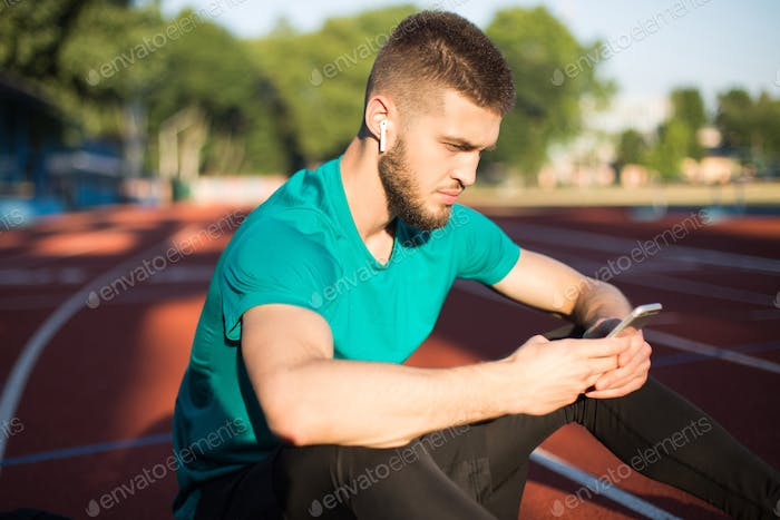 Man in wireless earphones thoughtfully using cellphone on running track of stadium