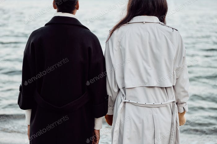 Close up back view of two stylish girls in trench coats standing by the sea