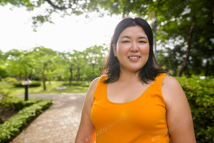 Beautiful overweight Asian woman smiling in park
