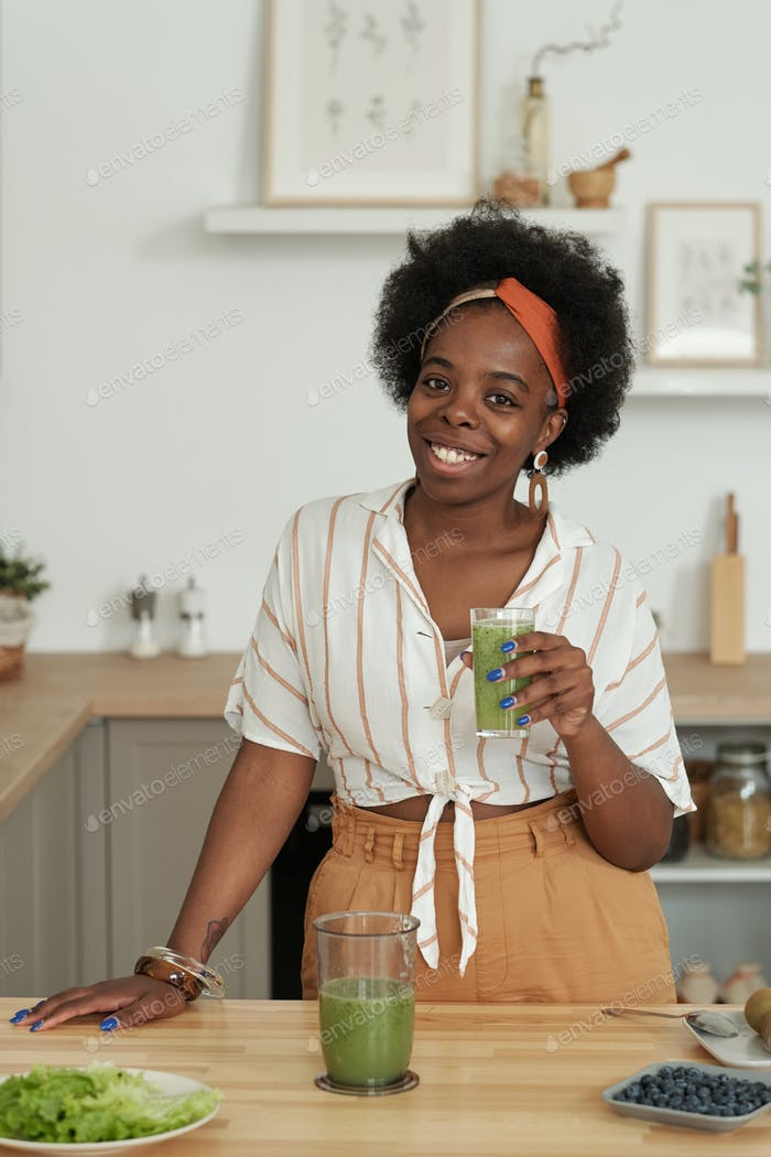 Young cheerful African woman with glass of smoothie