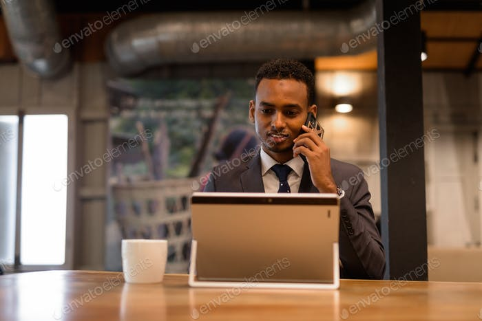 Businessman using laptop computer and talking at phone at coffee shop