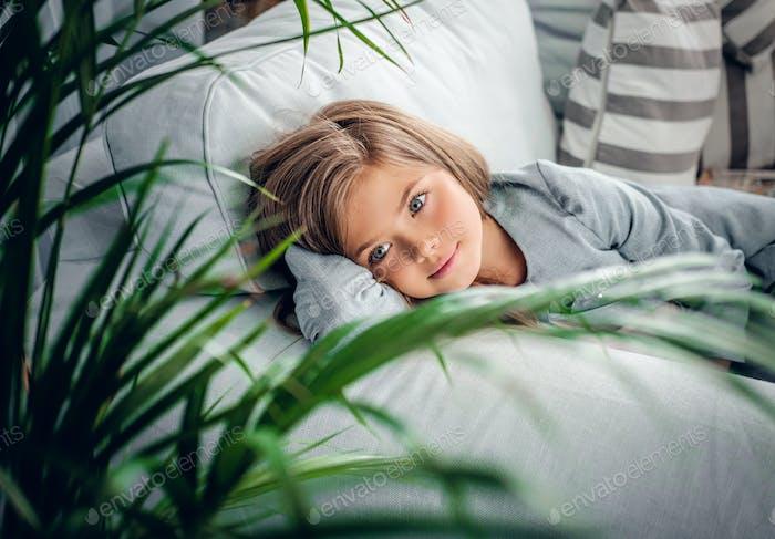 Una chica posando en un sofá en una sala de estar.