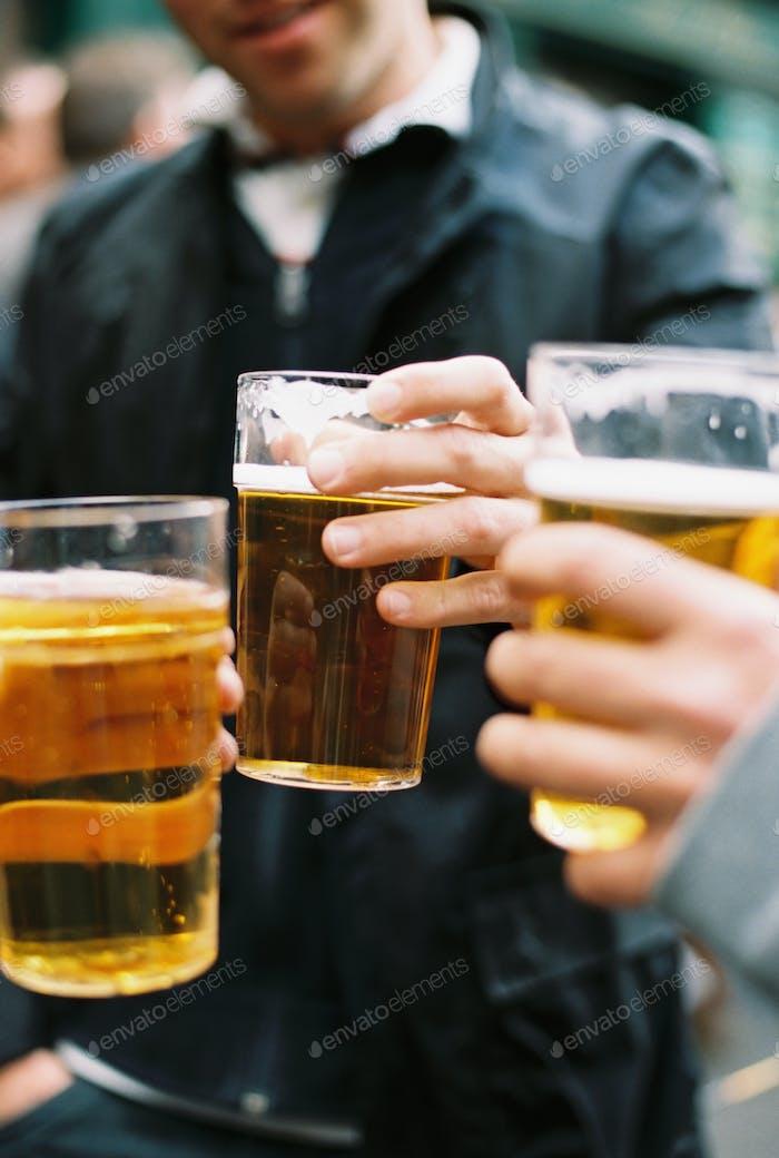 Drei Leute trinken Bier, klingeln Gläser und toasten sich gegenseitig.