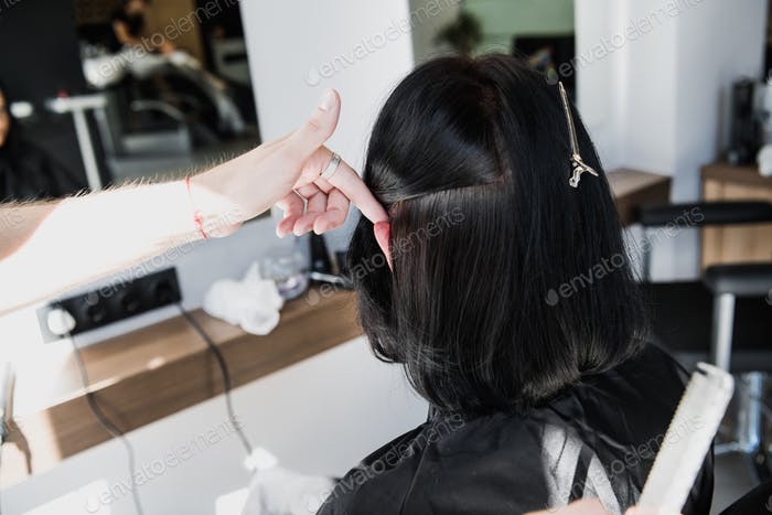 Professional hairdresser, stylist combing hair of female client in professional hair salon. Beauty