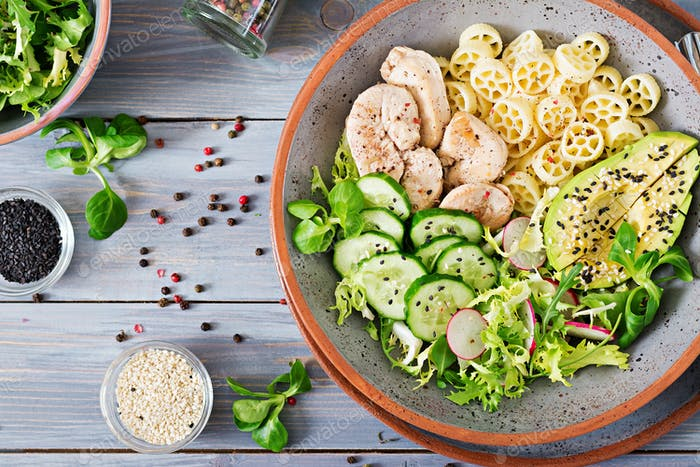 Healthy salad with chicken, avocado, cucumber, lettuce, radish  and pasta