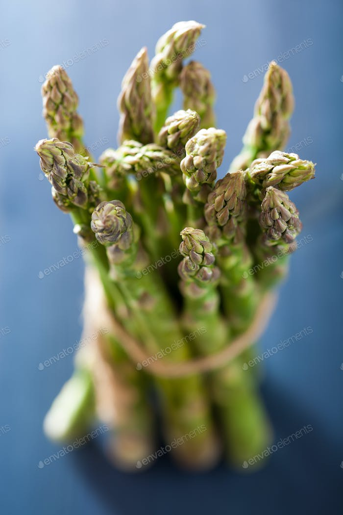 bunch of fresh asparagus on blue background