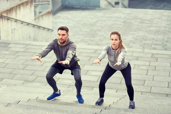 couple doing squats and exercising outdoors