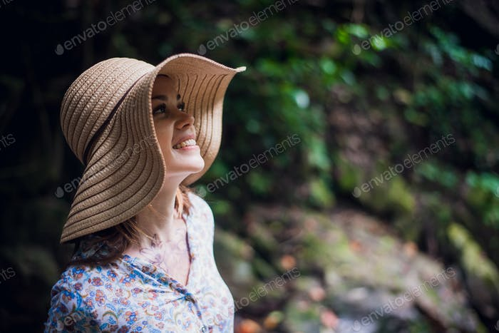 Portrait of young attractive female smiling in a jungle forest, summer vacation. Young woman