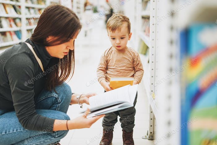 Cute baby boy toddler child in bookstore with mother