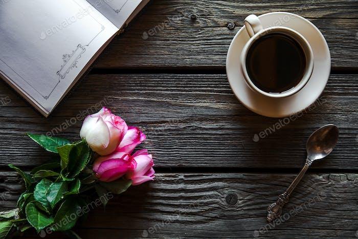 Frische Rosen mit Tagebuch und Tasse Kaffee auf Holztisch, von oben Ansicht. Blumen, Heißgetränk