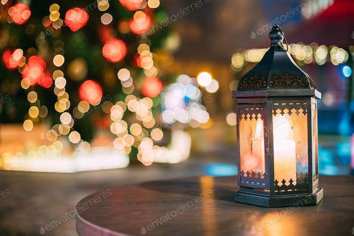 Christmas Lantern With Burning Candle On Bright Blurred Christma