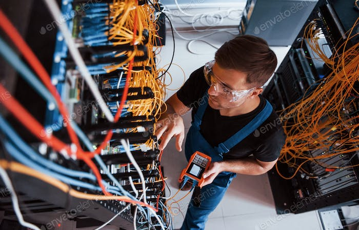 Young man in uniform that works with wires in server room