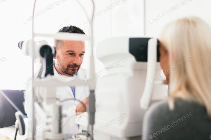 Optician examining his patient's eyes