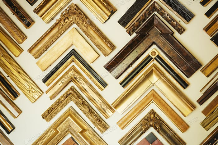 Interior view of a picture framers workshop, a large selection of frame samples on the walls.