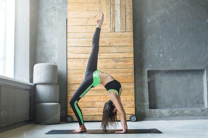 Young woman in yoga class, wheel pose