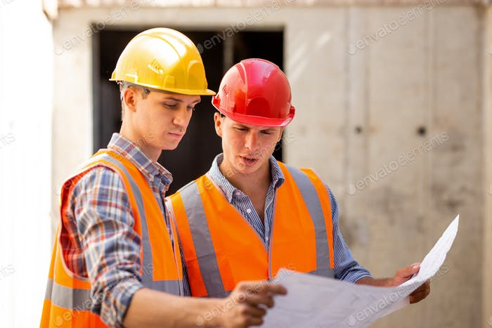Structural engineer and construction manager dressed in work clothes and hard bats explore