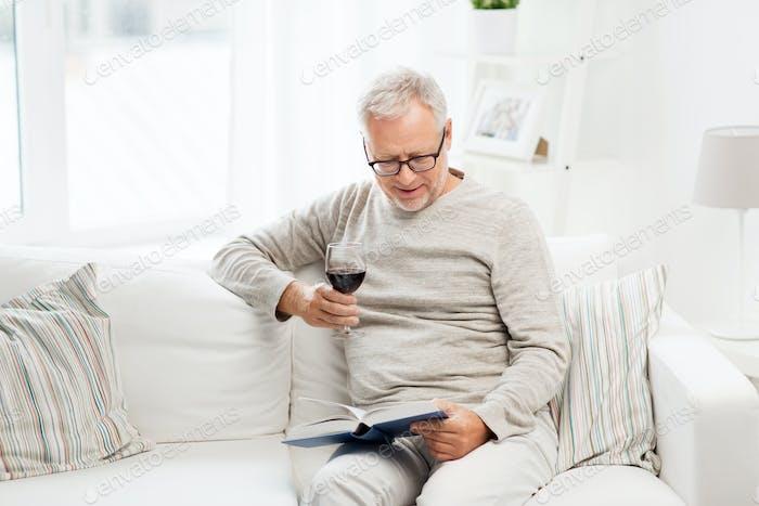 glücklich Senior Mann Wein trinken und Buch lesen