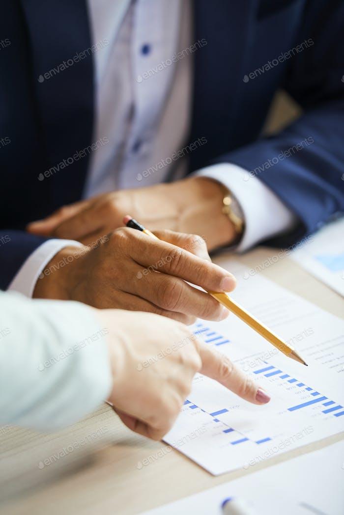 Geschäftsleute, die auf Chart zeigen