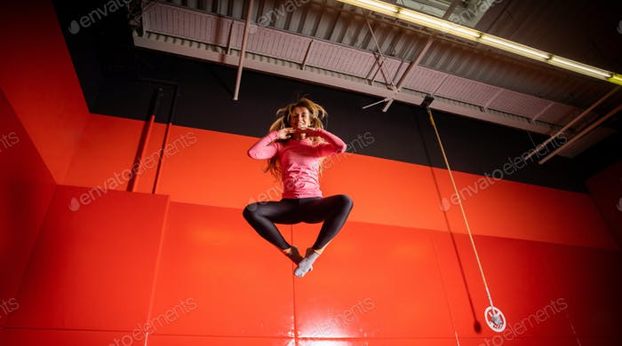 Houng fit happy woman jumping on trampoline in fintess center