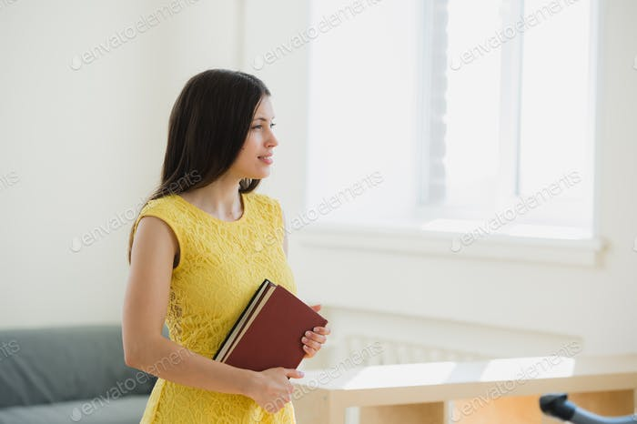 Happy pretty young female student with long black hair clutching school books to her chest as she