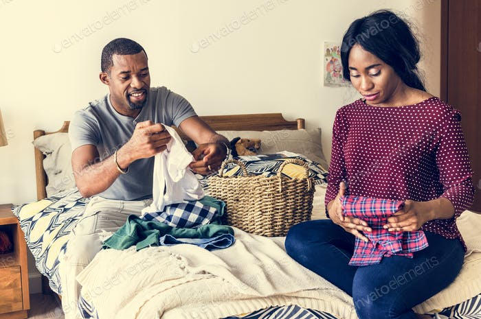Black couple folding clothes together