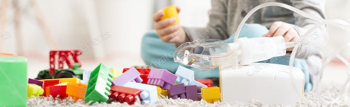 Kid with toys and asthma inhaler