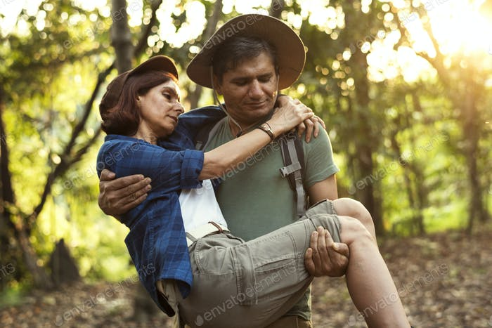 Man holding his partner up while trekking in the jungle