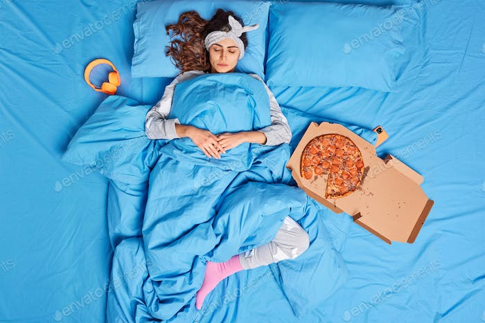 Calm millennial woman takes nap lies under soft blanket eats delicious pizza stays in bed enjoys goo
