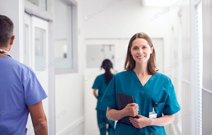 Portrait Of Smiling Female Doctor Wearing Scrubs In Busy Hospital Corridor Holding Digital Tablet