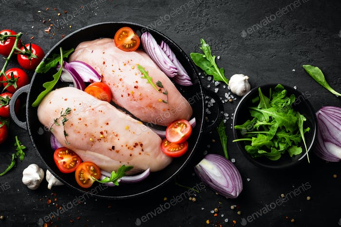 Fresh raw chicken eat, fillet marinated with spices, onion and tomatoes. Top view