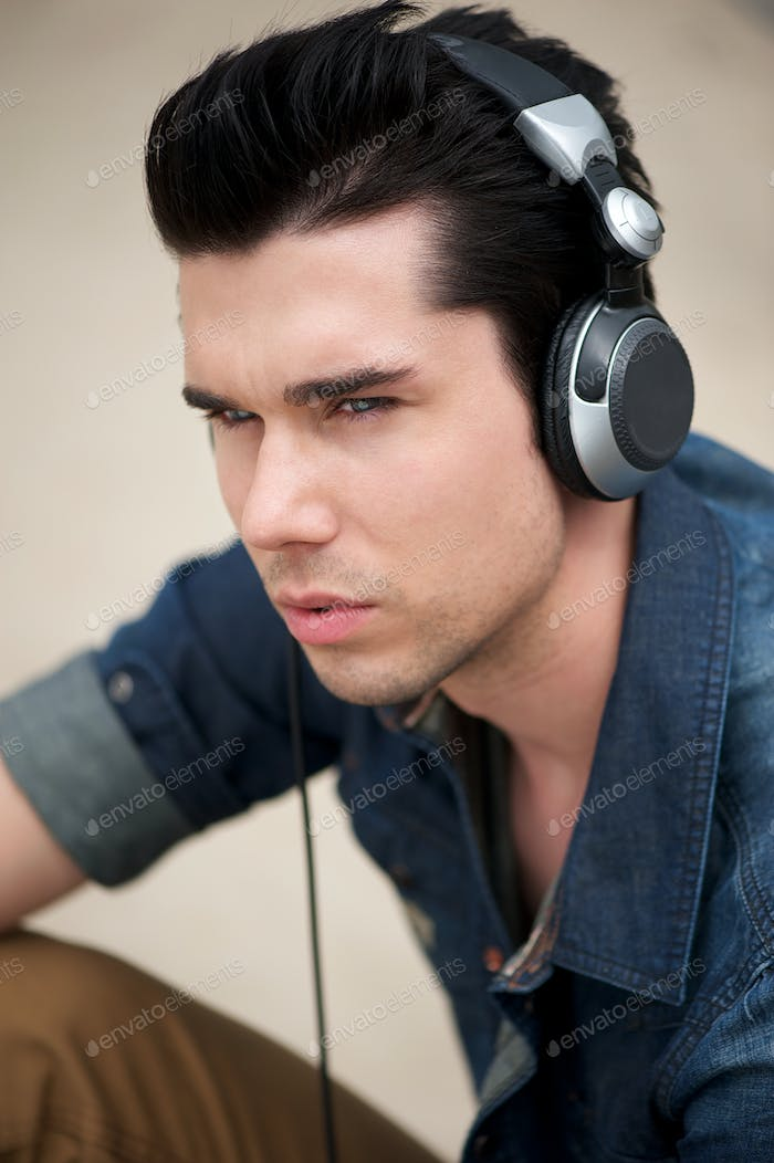 Attractive man listening to music on headphones outdoors