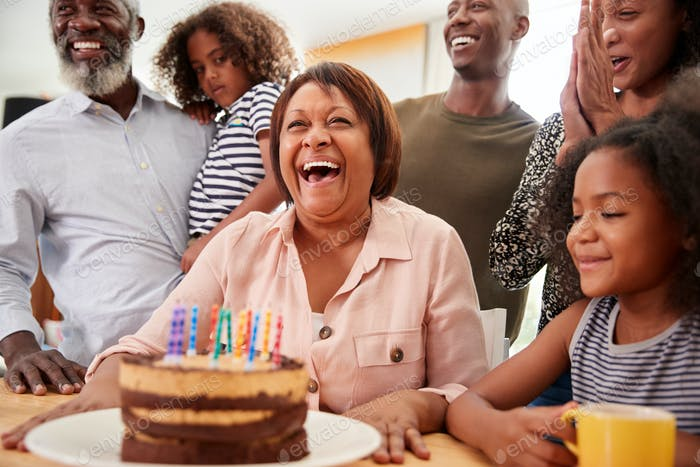Multi-Generation Family Celebrating Grandmothers Birthday At Home With Cake And Candles