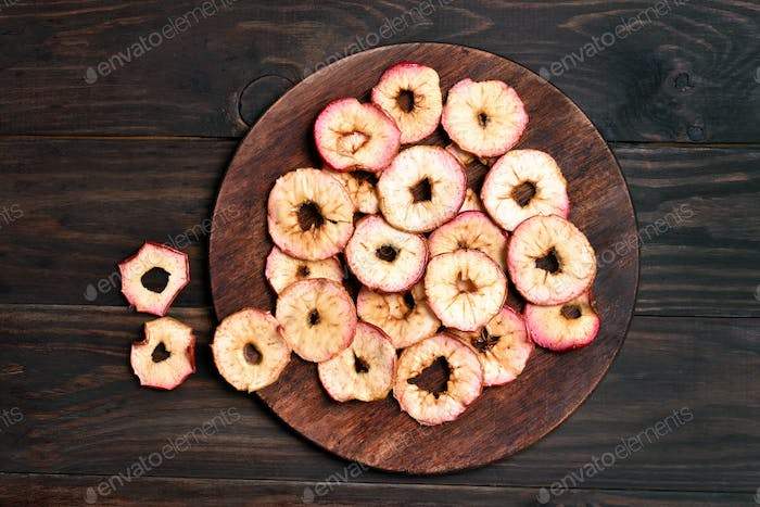 Apples chips on wooden board