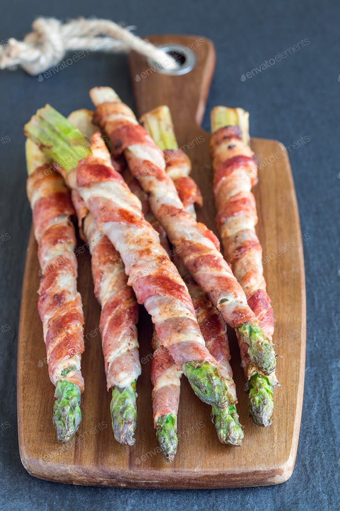 Healthy appetizer, green asparagus wrapped with bacon on a woode