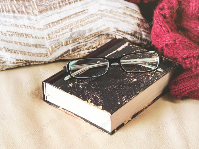 Glasses and book on leather sofa