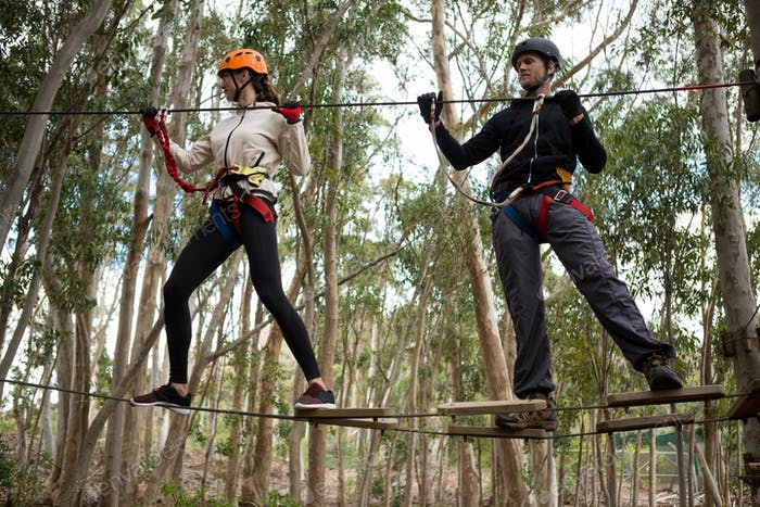 Couple holding zip line while crossing obstacle