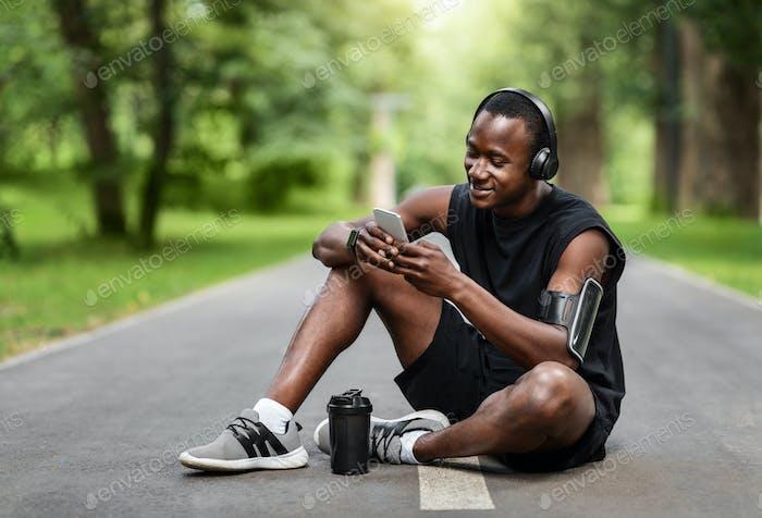Müde afrikanische Sportler sitzen auf Parkweg, mit Smartphone