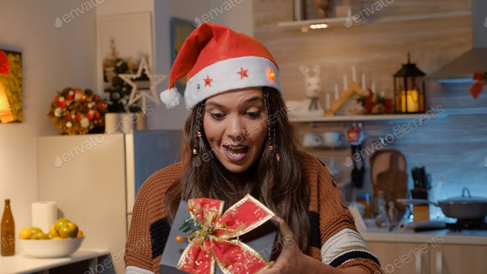 Festive woman with santa hat receiving gift