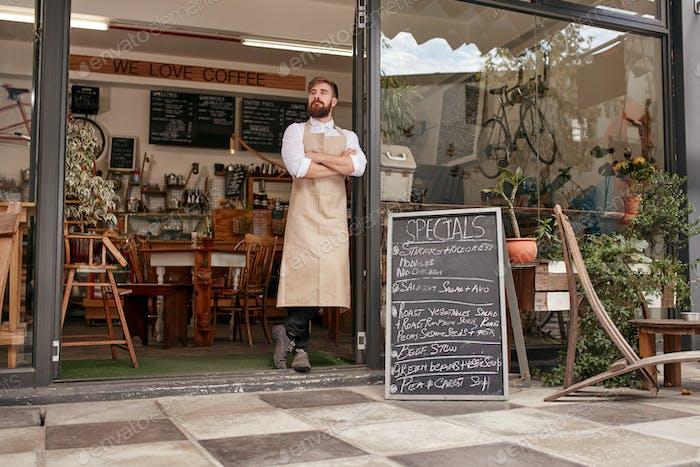 Barista steht in der Tür eines Cafés